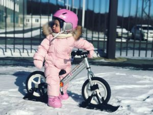 Girl on Strider 12 with Snow Ski Attachment
