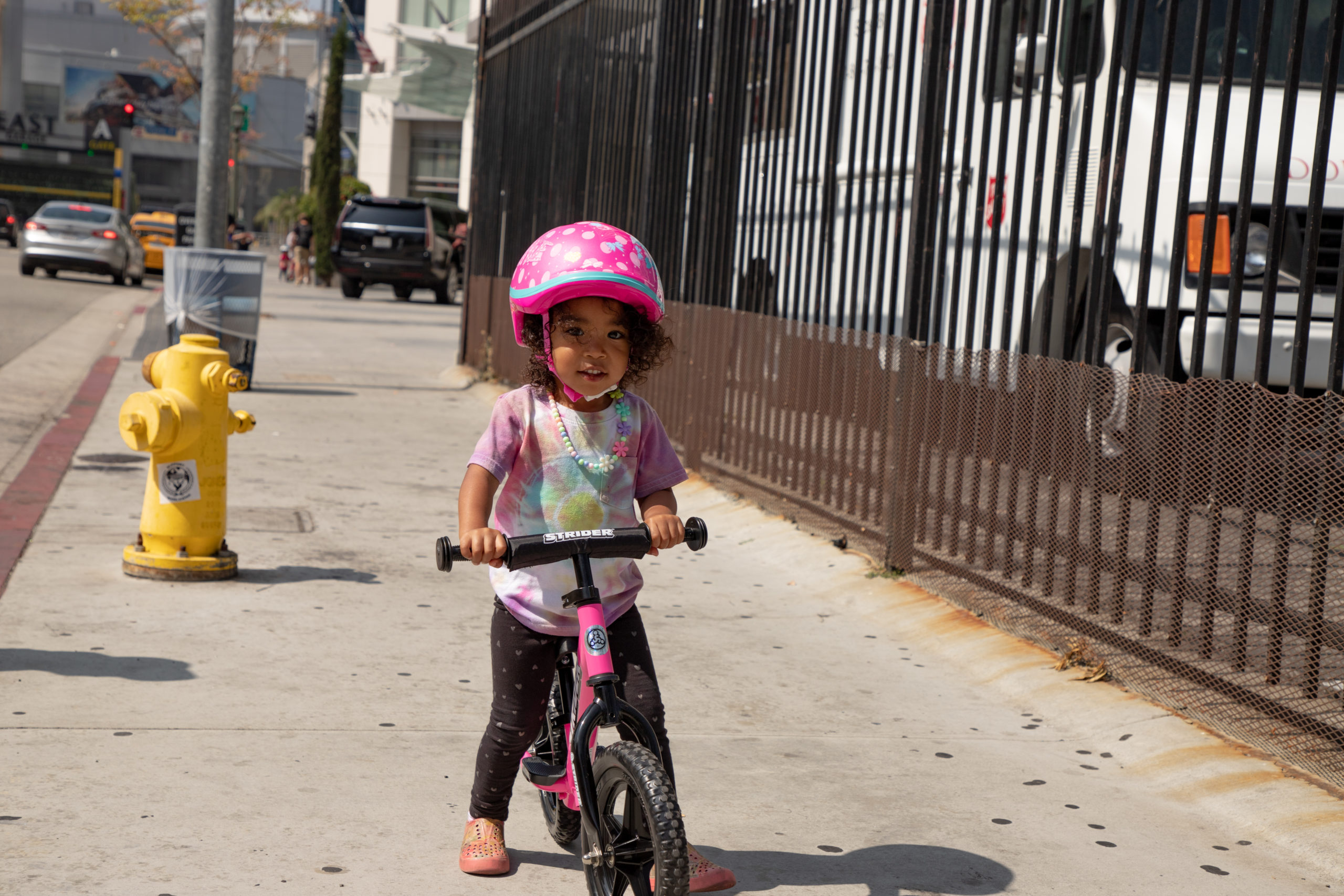 Young girl riding on sidewalk on pink 12 sport