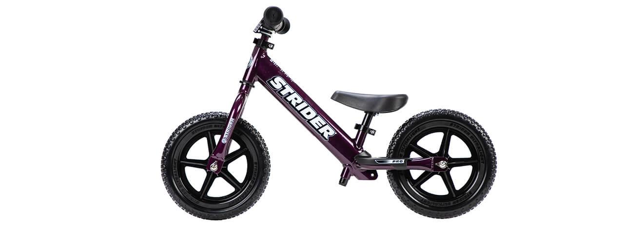A studio profile picture of a purple Strider 12 Pro balance bike