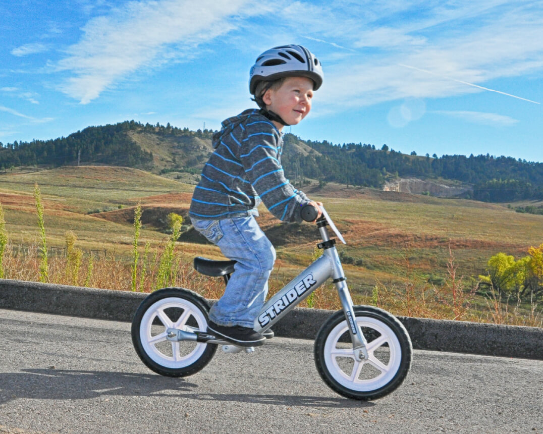 Boy riding Strider balance bike in countryside