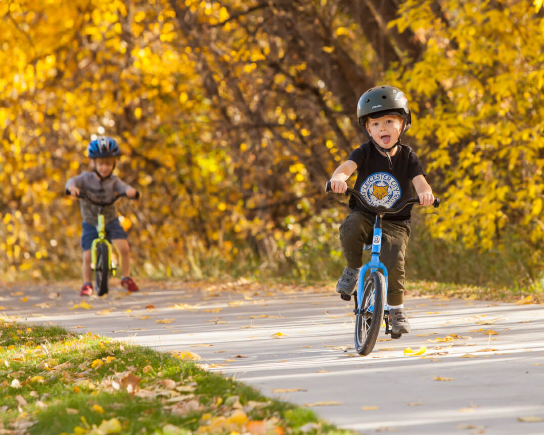 kids riding Strider 14x balance bike on bike path