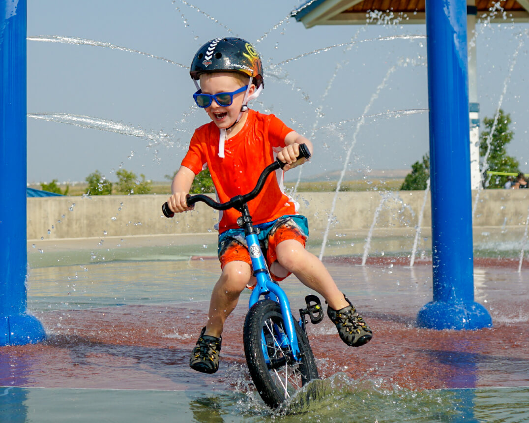 boy riding Strider 14x balance bike at water park