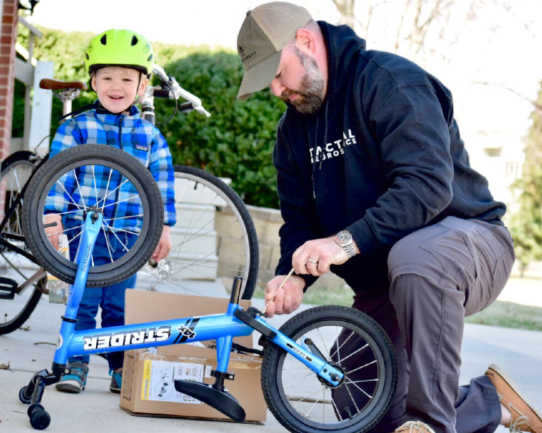 Dad helping son with Strider 14x balance bike