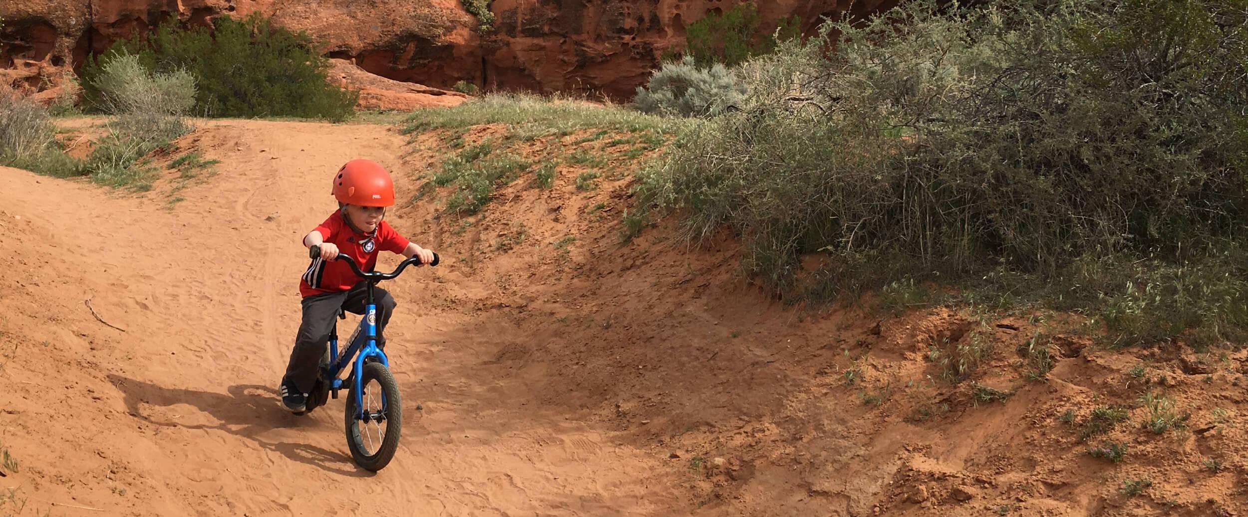 child riding Strider 14x balance bike on dirt track