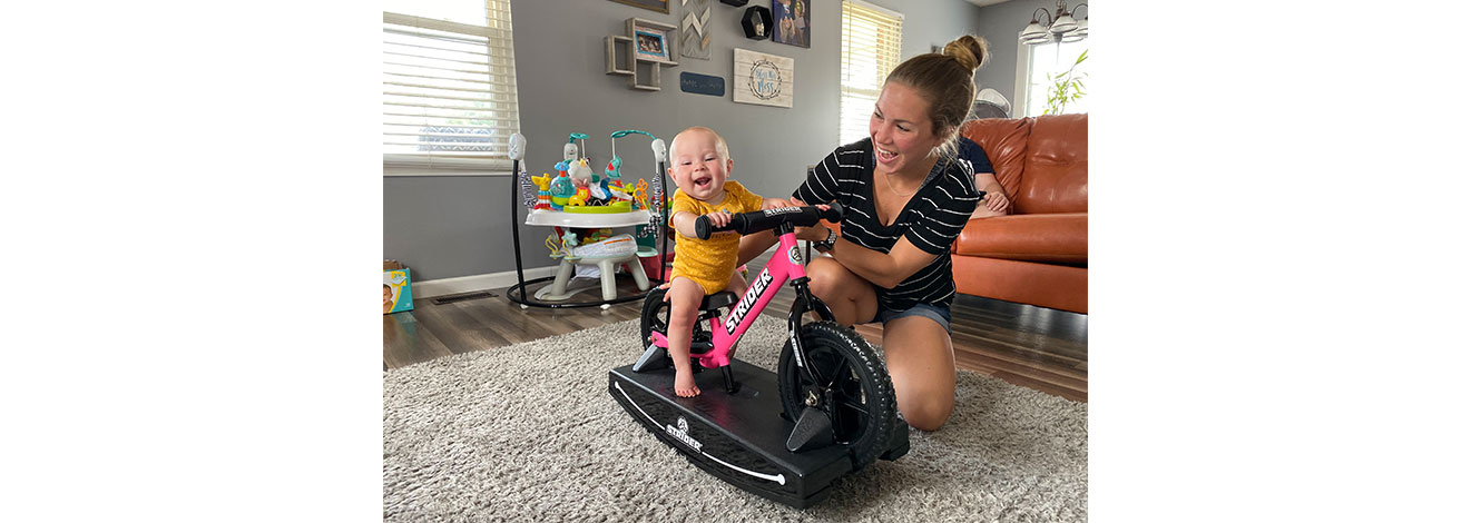 Mom holding baby on pink 2-in-1 Rocking Bike