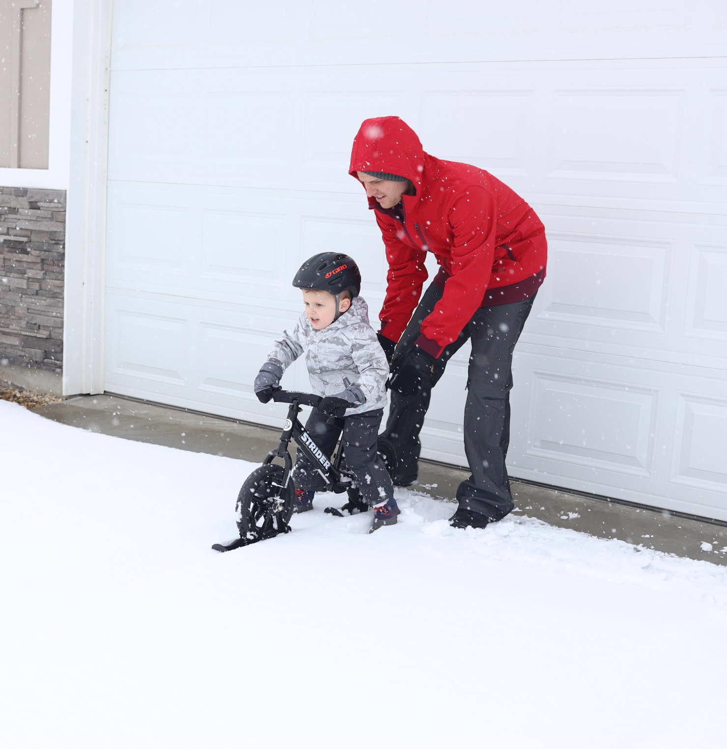 Dad supporting kid on black 12 Sport with skis attached
