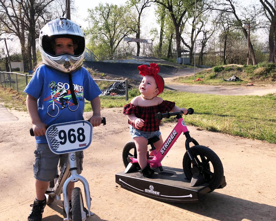Boy on Strider Balance Bike and baby on Strider Baby Bundle