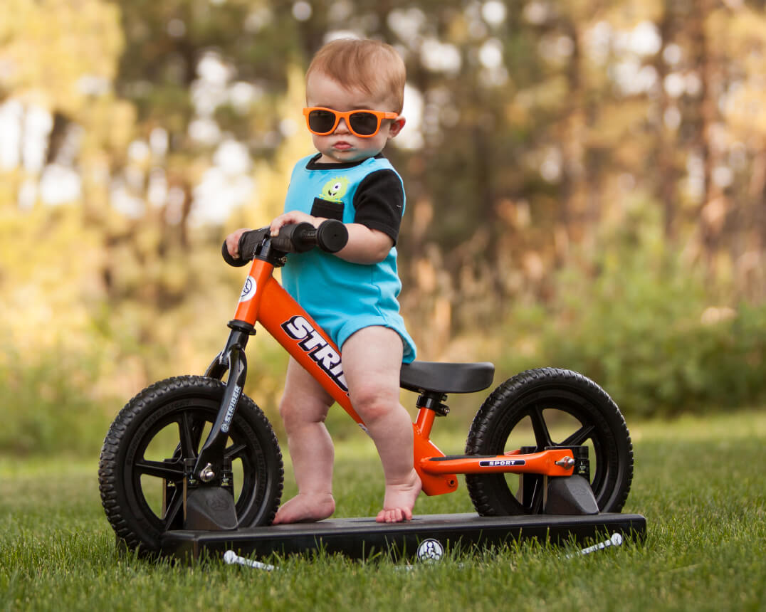 Baby with sunglasses on Strider Baby Bundle Balance Bike