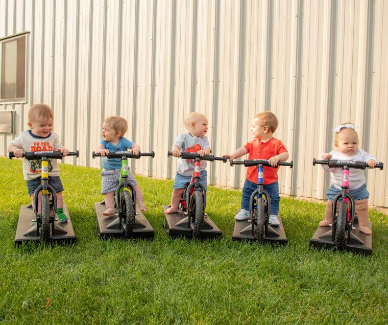 babies riding Strider Baby Bundle balance bikes