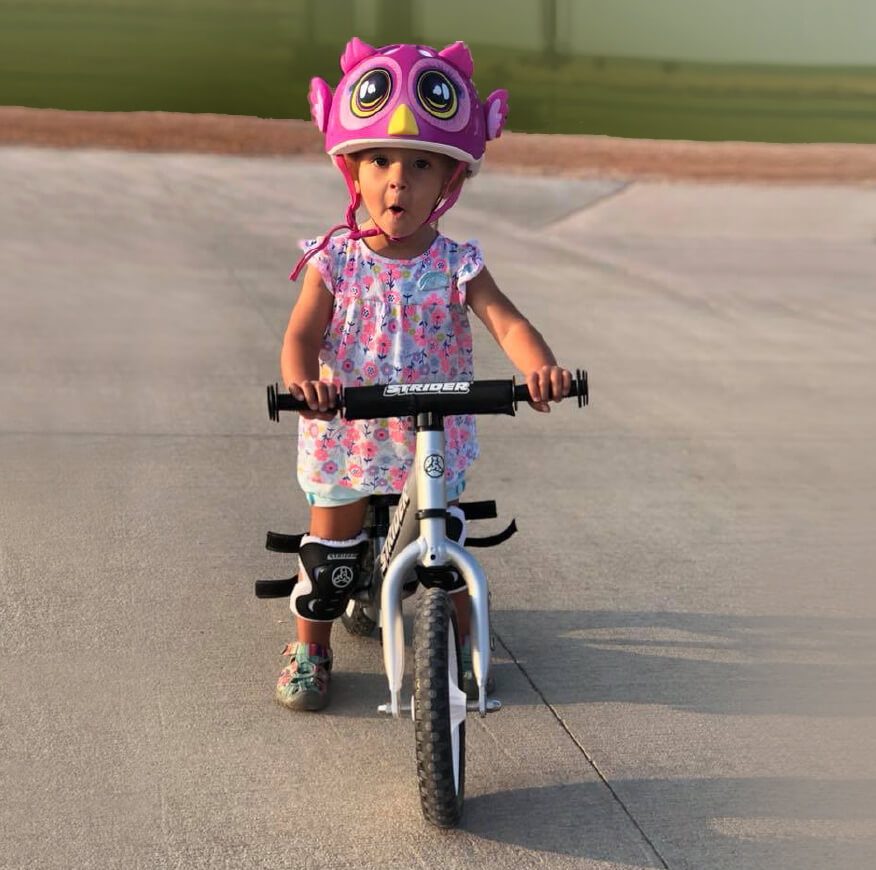 Cute girl with owl helmet on Strider Balance Bike