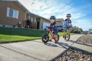 Boy on red Strider Balance Bike and Boy on green Strider 14x Sport