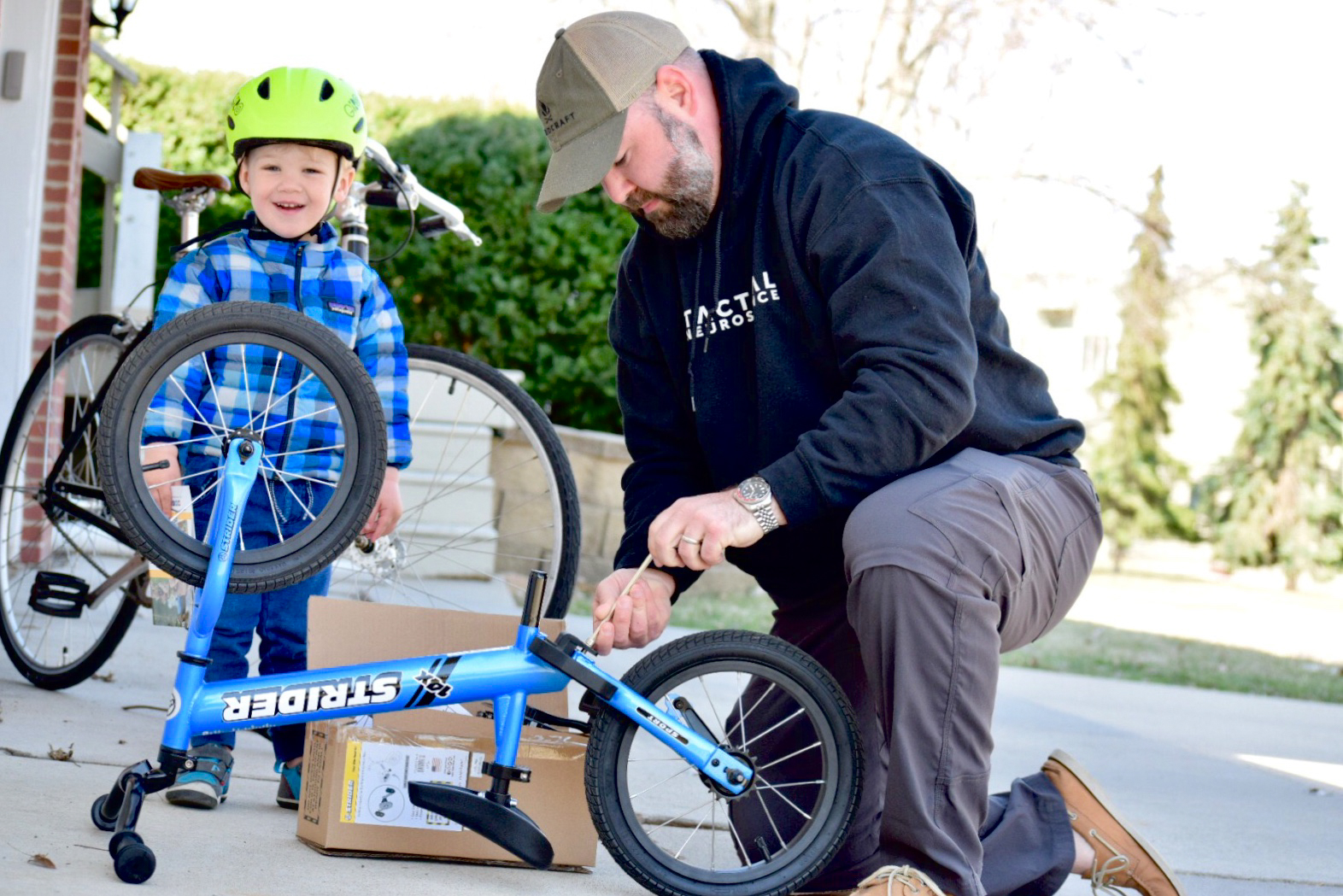 Dad helping attach Easy-Ride Pedal Kit to Strider 14x Sport blue bike with kid watching