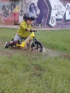 Boy riding through puddle on yellow Strider Sport Balance Bike