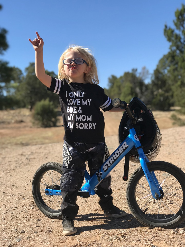 Boy giving rock-on sign on blue Strider 14x Sport