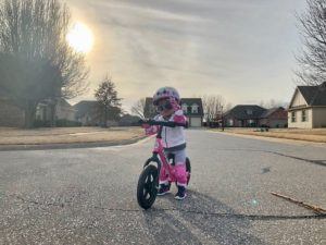 Girl with sunglasses on pink Strider Balance Bike
