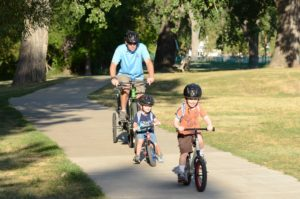 Dad and Kids riding Strider Balance Bikes