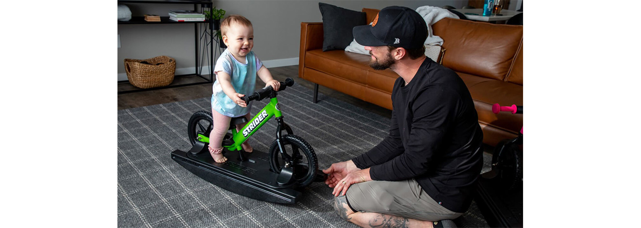 A baby on a green Rocking Bike laughs with Dad