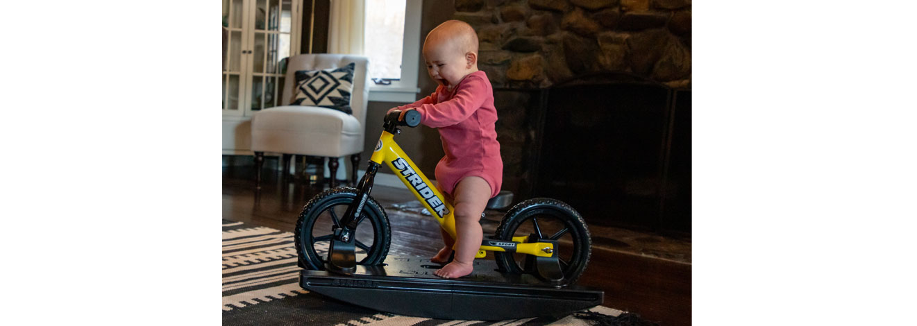 A baby riding on a yellow Strider 2-in-1 Rocking Bike in the living room