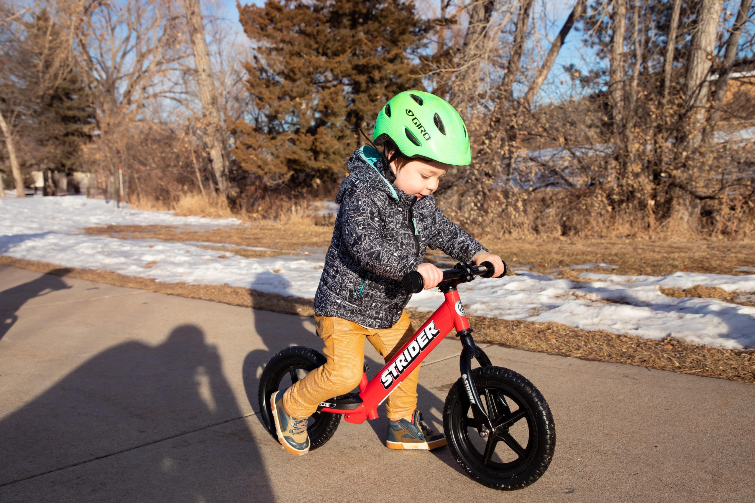 Toddler boy striding on red 12 Sport with Strider Aluminum Flat Handlebar