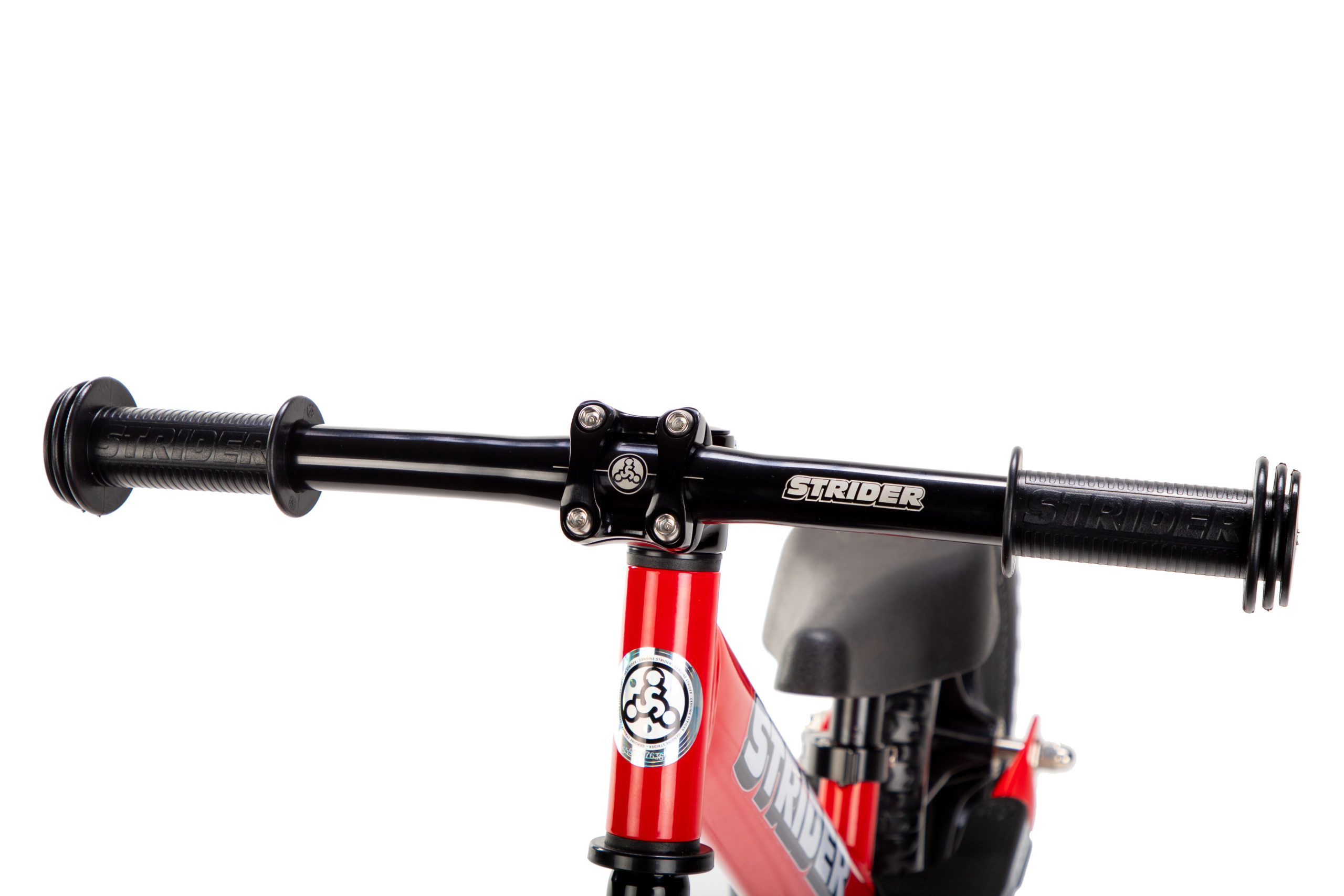Studio image of Strider Aluminum Flat Handlebar with Grips on red 12 Sport - close-up angled view