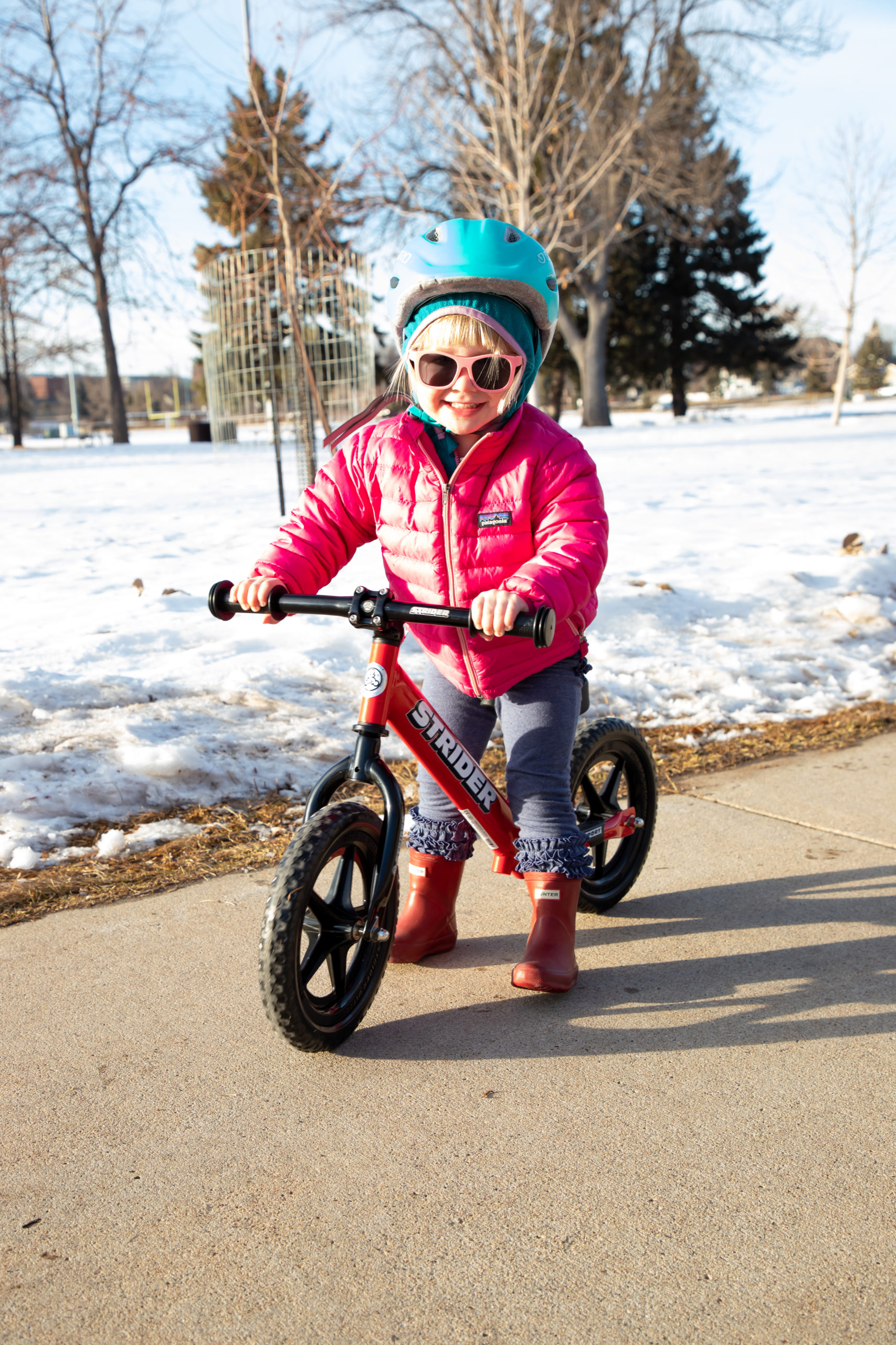 Girl posing with sunglasses on red 12 Sport with Strider Aluminum Flat Handlebar with Grips