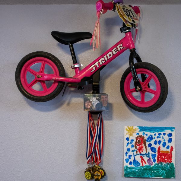 A pink Strider 12 Classic balance bike mounted to the wall with a Strider Memory Mount